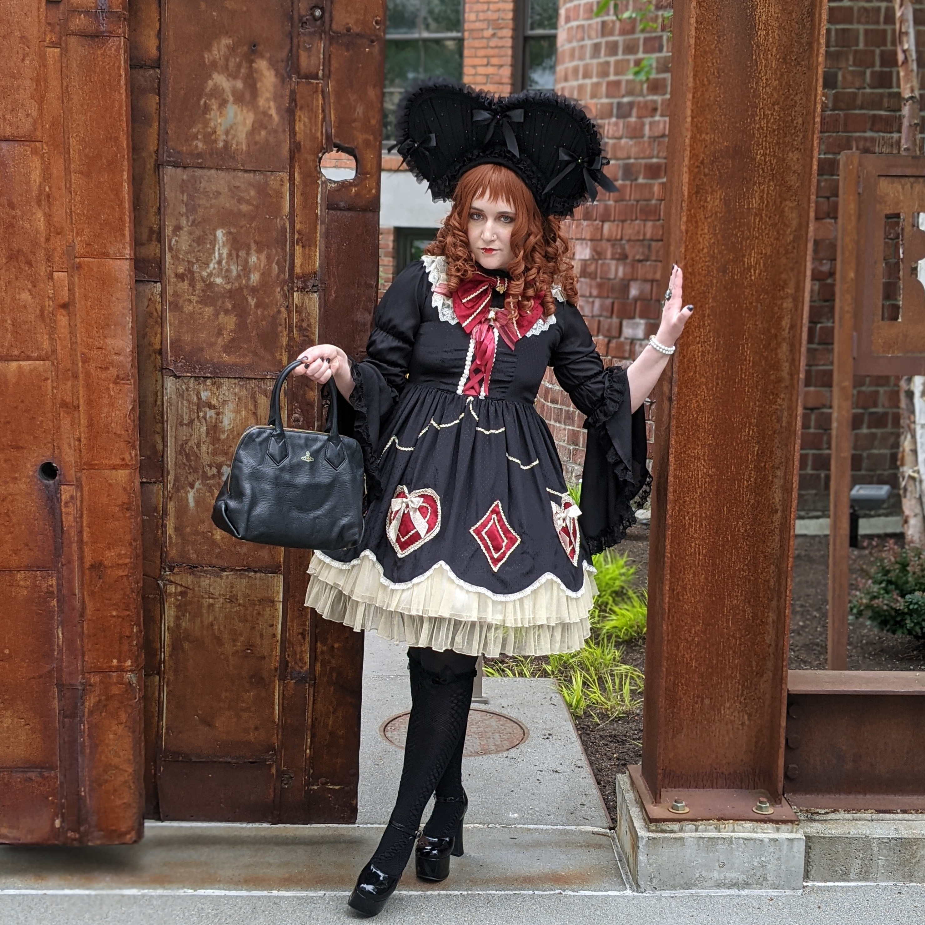 Nif, a white femme wearing a curled auburn wig, wears BTSSB's White Rabbit's Heart Cards in black. She is wearing the Empire Noir Sull'Amore bonnet in black, a large, heart-shaped headdress. She is wearing an Atelier Pierrot blouse with princess sleeves, black fishnet stockings over black tights, and dramatic black heels. She is holding a Vivienne Westwood bag in her right hand, and wearing a bracelet and a ring on her left hand. She is wearing a red pinbow like a bow tie. She is standing in a rusted metal and wood doorway.